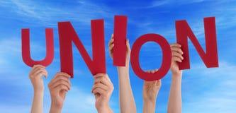 Muchas manos de la gente que sostienen el cielo azul de la unión roja de la palabra Foto de archivo