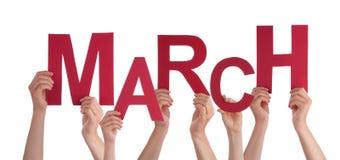 Muchas manos de la gente que sostienen el cielo azul de marzo de la palabra roja Imagen de archivo libre de regalías
