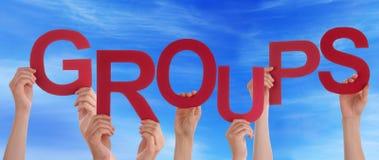 Muchas manos de la gente que sostienen el cielo azul rojo de los grupos de palabra Fotos de archivo libres de regalías