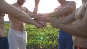 Muchas manos del varón que se reúnen Equipo de atletas que ponen los brazos juntos al aire libre Manos que se unen a del grupo de almacen de video