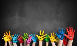 Muchas manos pintadas de los niños con smiley Fotos de archivo libres de regalías