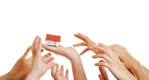 Muchas manos que alcanzan para la casa Imágenes de archivo libres de regalías