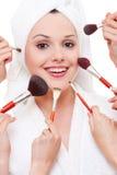 Muchas manos que aplican maquillaje a la mujer hermosa Foto de archivo libre de regalías