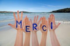 Muchas manos que construyen los medios de Merci agradecen le, la playa y el océano imagenes de archivo