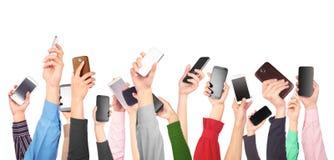Muchas manos que sostienen los teléfonos móviles Fotos de archivo libres de regalías