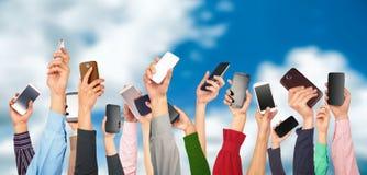 Muchas manos que sostienen los teléfonos móviles contra Imagen de archivo libre de regalías