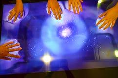 Muchas manos y pantalla táctil grande Imagenes de archivo