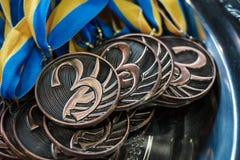 Muchas medallas de bronce con las cintas de cobre y las cintas azules amarillas en una bandeja de plata, premios de los campeones foto de archivo libre de regalías