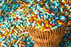 Muchas medicinas coloridas expiran en el paquete de bambú de la cesta de armadura Fotografía de archivo libre de regalías