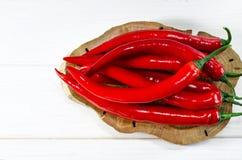 Muchas mentiras rojas de los chiles de los pepers en un tablero oval de Brown, que se coloca en una tabla de madera blanca fotos de archivo