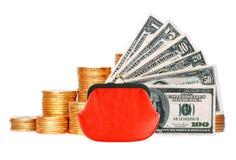 Muchas monedas en la columna, el monedero rojo y los dólares aislados en blanco Imágenes de archivo libres de regalías