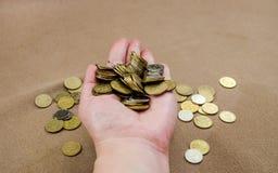 Muchas monedas en la mano femenina imagen de archivo