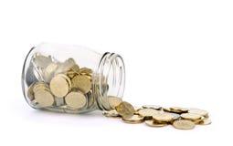 Muchas monedas que se derraman fuera de un tarro de cristal y aisladas Foto de archivo libre de regalías