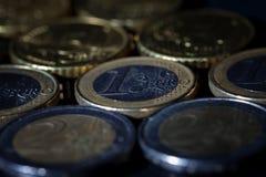 Muchas monedas y centavos euro en negro imagen de archivo