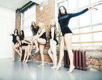 Muchas muchachas que entrenan en el ballet del estudio, el apoyar atractivo de las piernas largas de la mujer, mono negro sexual  imagen de archivo