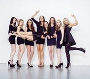 Muchas mujeres diversas en línea, pequeños vestidos de lujo del negro que llevan, van de fiesta el maquillaje, concepto del vice  Foto de archivo