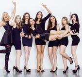 Muchas mujeres diversas en línea, pequeños vestidos de lujo del negro que llevan, van de fiesta el maquillaje, concepto del vice  Foto de archivo libre de regalías