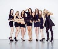 Muchas mujeres diversas en línea, pequeños vestidos de lujo del negro que llevan, van de fiesta el maquillaje, concepto del vice  Fotos de archivo