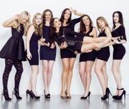 Muchas mujeres diversas en línea, pequeños vestidos de lujo del negro que llevan, van de fiesta el maquillaje, concepto del vice  Imágenes de archivo libres de regalías