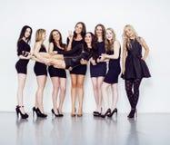 Muchas mujeres diversas en línea, pequeños vestidos de lujo del negro que llevan, van de fiesta el maquillaje, concepto del vice  Fotografía de archivo libre de regalías