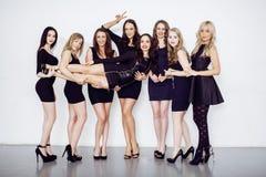 Muchas mujeres diversas en línea, pequeños vestidos de lujo del negro que llevan, van de fiesta el maquillaje, concepto del vice  Fotos de archivo libres de regalías