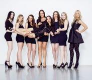 Muchas mujeres diversas en línea, pequeños vestidos de lujo del negro que llevan, van de fiesta el maquillaje, concepto del vice  Imagenes de archivo
