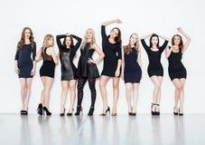 Muchas mujeres diversas en línea, pequeños vestidos de lujo del negro que llevan, van de fiesta el maquillaje, forma de vida del  Fotografía de archivo libre de regalías