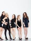 Muchas mujeres diversas en línea, pequeños vestidos de lujo del negro que llevan, van de fiesta el maquillaje, forma de vida del  Fotos de archivo libres de regalías
