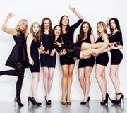 Muchas mujeres diversas en línea, pequeños vestidos negros de lujo que llevan, Imagenes de archivo