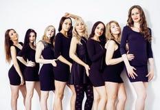 Muchas mujeres diversas en línea, pequeños vestidos negros de lujo que llevan, Foto de archivo libre de regalías