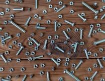 Muchas nueces - y - pernos en una superficie de madera imagenes de archivo