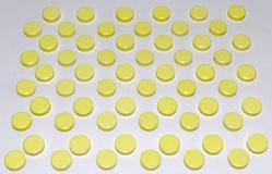 Muchas píldoras amarillas, dispuestas en orden escalonada Imagen de archivo libre de regalías
