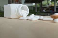 Muchas píldoras/tabletas blancas/medicina en la placa de madera Imagenes de archivo