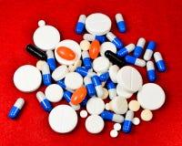Muchas píldoras y cápsulas en fondo rojo Imagenes de archivo