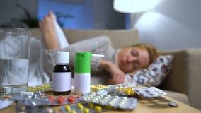 Muchas píldoras y medicinas en una tabla en Front Of una mujer joven enferma en el sofá almacen de metraje de vídeo