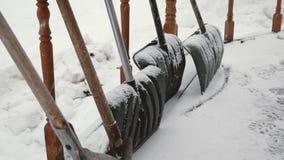 Muchas palas que se colocan en el pórtico de la casa en nevadas pesadas en invierno metrajes