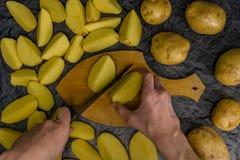 Muchas patatas en la tabla y en una tabla de cortar Patatas, cortadas en una tabla de cortar Limpieza de la patata en la tabla Cu foto de archivo libre de regalías