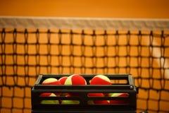 Muchas pelotas de tenis a las bolas de la cesta, campo de tenis Rejilla para el tenis Imagen de archivo