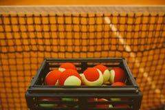 Muchas pelotas de tenis a las bolas de la cesta, campo de tenis Rejilla para el tenis Fotografía de archivo