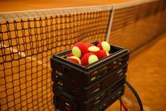 Muchas pelotas de tenis a las bolas de la cesta, campo de tenis Rejilla para el tenis Fotos de archivo libres de regalías