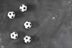 Muchas pequeñas bolas del fútbol en fondo texturizado negro de la pizarra con el espacio de la copia para el texto y el diseño Vi fotografía de archivo