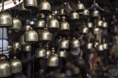 Muchas pequeñas campanas de cobre amarillo de cobre amarillo que cuelgan en el pequeño recuerdo Imagenes de archivo