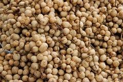 Muchas pequeñas frutas del longan están en el mercado asiático imagen de archivo libre de regalías