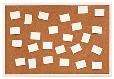 Muchas pequeñas hojas de papel en tablero del corcho del boletín Imagenes de archivo