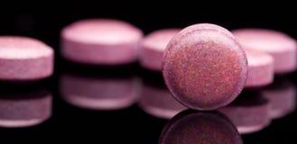 Muchas pequeñas píldoras rojas, grupo de vitaminas Píldoras rojas en vagos negros Imagenes de archivo