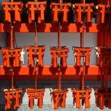 Muchas pequeñas puertas rojas del torii Imagenes de archivo