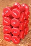 Muchas pesas de gimnasia rojas que pesan un kilogramo Foto de archivo