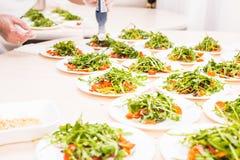 Muchas placas con la ensalada fresca con el arugula de la carne, de los tomates, nuts y mezclado de los verdes, mesclun, mache en Fotos de archivo libres de regalías