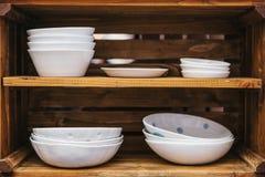 Muchas placas de cerámica ordinarias en estantes de madera Accesorios de la cocina para cocinar imagen de archivo libre de regalías