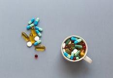 Muchas píldoras coloridas en taza en fondo gris Fotografía de archivo libre de regalías